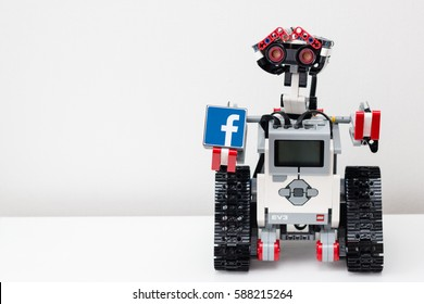 Minsk, Belarus -  February 26, 2017: Lego robot is holding a cube with the logo of the world's most famous social network Facebook.  Like. School. E-learning.  STEM education.