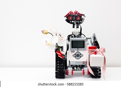 Minsk, Belarus -  February 26, 2017: Lego robot has prepared a gift - the Pandora jewelery box and beautiful orchid flower. Gold and silver jewelry. School. E-learning.  STEM education.