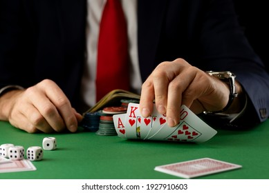 Minsk, Belarus, February 7, 2021. A businessman at a green gaming table with gambling chips and cards playing poker and blackjack in a casino.