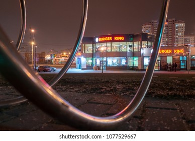 MINSK, BELARUS - JANUARY 14, 2018: Bicycle parking near the Burger King fast food hamburgers restauran at night time near the Kamennaya horka metro station in Minsk.