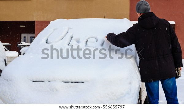 Minsk, Belarus - January 15, 2017: A man writes on a car littered with snow Company logo Uber.