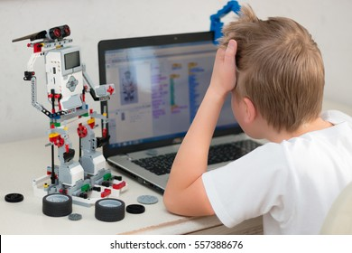 Minsk, Belarus - January 16, 2017: Boy teenager behind the desk programs Lego robot on the laptop ASUS in Scratch program.