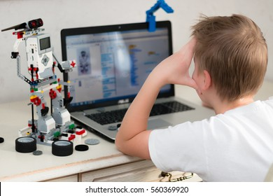Minsk, Belarus - January 16, 2017: Boy teenager behind the desk programs Lego robot on the laptop in Scratch program.