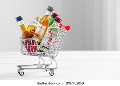 Minsk, Belarus - January 16, 2018: mini shopping cart full of small alcohol bottles - Jameson whiskey, Camus and Martell cognacs, Havana club rum, Beefeater gin. Minsk, Belarus.