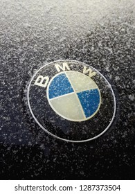 Minsk, Belarus - January 17, 2019 : BMW logo on the snow-covered hood of the black car