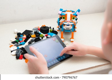 Minsk, Belarus. January, 2018. A teenager boy is programming a robot on iPad Apple. A cat assembled from a Lego Boost constructor named Franky. Classes on robotics. STEM education.