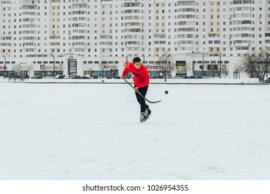 Minsk Belarus January 21, 2018 Walking on the ice of a frozen river A guy with a stick plays ice hockey