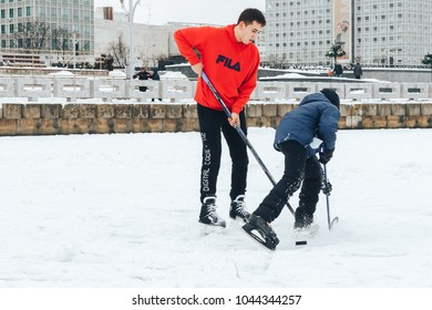 Minsk Belarus January 21, 2018 Walking on the ice of a frozen river Boy and boy playing hockey