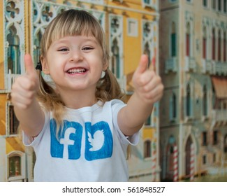 Minsk, Belarus - January 22, 2017: Little girl in a white T-shirt with logos painted manually Facebook and Twitter. Cute smiling and pricks Like.