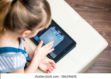 Minsk, Belarus - January 22, 2017: Little girl teenager is on the floor and registered in the social network on iPad Apple. Twitter. Facebook. Skype. Viber. E-learning. Modern technology in education.