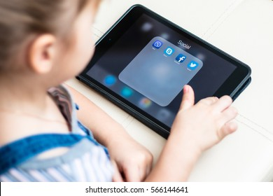 Minsk, Belarus - January 22, 2017: Little girl teenager is on the floor and registered in the social network on iPad Apple. Twitter. Facebook. Skype. Viber. E-learning. Modern technology in education.