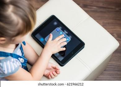 Minsk, Belarus - January 22, 2017: Little girl is registered in the social network on iPad Apple. Twitter. Facebook. Skype. Viber. E-learning. Modern technology in education.