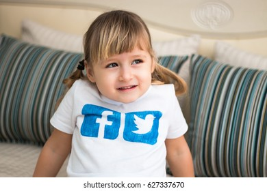 Minsk, Belarus - January 22, 2017: Little girl is in a white T-shirt with  painted logos of Facebook and Twitter.  She is smiling. Cute baby.