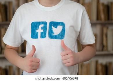 Minsk, Belarus - January 24, 2017: Boy teenager in a white T-shirt, with painted logos of popular social networks Facebook and Twitter, shows with his hand Like.