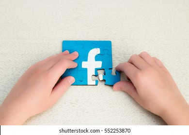 Minsk, Belarus - January 8, 2017: Facebook logo. Teen drawing on the puzzles. Handmade. Child puts puzzles. Fashion and famouse social network around the world.
