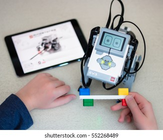 Minsk, Belarus - January 8, 2017: Teenager schoolboy controls the Lego Robot Dog with iPad. School Robotics. Modern training. The hottest gadgets. E-learning. Modern teaching technology. Education
