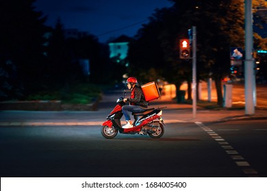 Minsk, Belarus. Jul 2019. Delivery man delivering online food orders on moto scooter at night. Young delivery boy with red thermal bag, restaurant courier carries food, quick deliver meal to costumer