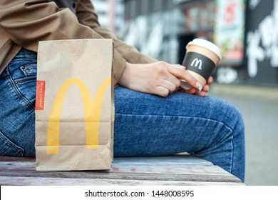 Minsk, Belarus, July 02, 2019: Takeout packing paper bag McDonald's on a bench next to a woman with paper cup of coffee in hand with McDonald's logo