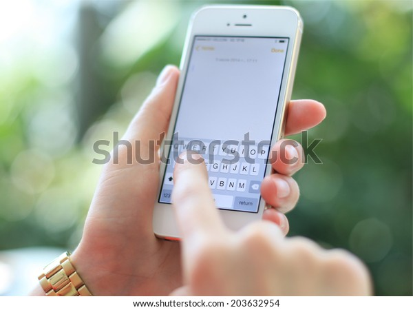MINSK, BELARUS - JULY 05, 2014: Woman holding brand new black Apple iPhone 5S. Skype is a voice-over-IP service and instant messaging client.