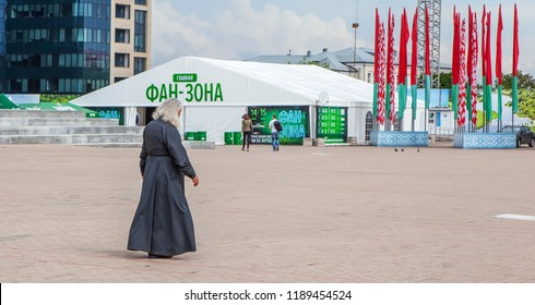 MINSK, BELARUS - JULY 14, 2018: Photo of Religion and sport. A priest on the background of the fan zone of the 2018 World Cup on October Square.