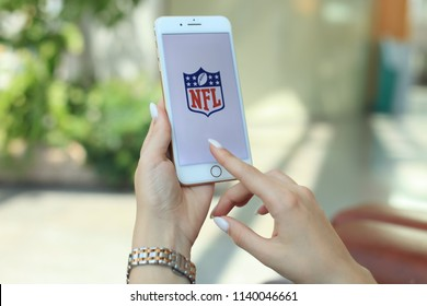 "MINSK, BELARUS – July 18, 2018: Woman holding brand new white Apple iPhone 7 plus. The logo of the brand ""NFL National Football League""."