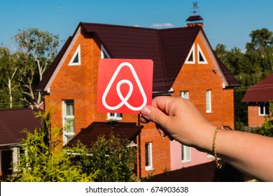 Minsk, Belarus - July, 2017: Travel around the world with Airbnb. Logo Airbnb. Home concept. Big house. Woman hand.