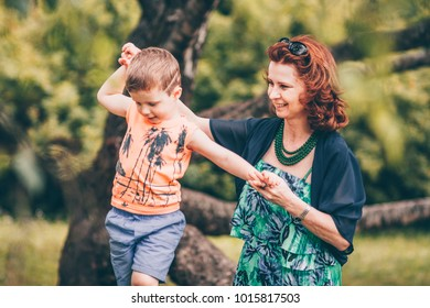 Minsk, Belarus, July 23, 2017: A caring mother supports and protects a boy who climbs a tree