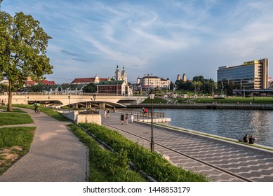 Minsk, Belarus - july 28, 2018. Panoramic view of Upper Town with Svislach River embankment, bridge, Trinity Hill with churches and historical buildings and walking people on riverbank.