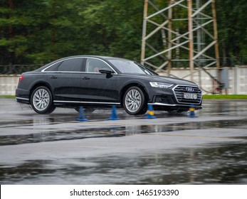 MINSK, BELARUS - JULY 28, 2019: Audi A8 65 TFSI Quattro 2019 model year drives on a wet asphalt road during test drive event. The car equipped with 4-litre V8 turbo producing 460 hp.
