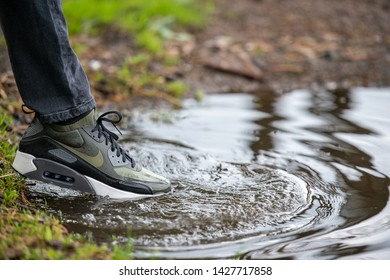 Minsk, Belarus - July 3, 2018: Nike Air Max 90 Ultra. Male leg in Nike Air max 90 stepping in the water to show the waterproof technology.