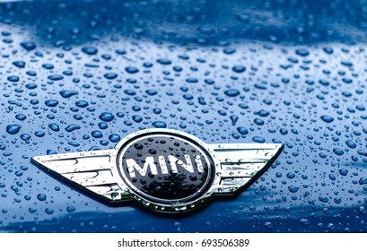 Minsk, Belarus, July 31, 2017: close-up of Mini Cooper car logo on a blue Mini Cooper car with rain drops