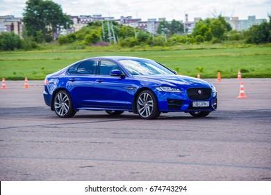 MINSK, BELARUS - JULY 7, 2017: Test-drive event for 2017 model year Land Rover and Jaguar is held in Minsk, Belarus on July 7, 2017. Dark Blue Jaguar XF is on display on the handling track.
