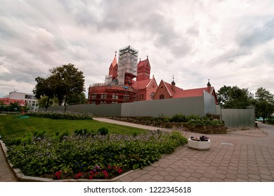 Minsk. Belarus - Jun.2018. Red Church of Saints Simon and Helena surrounded by scaffolding for renovation. Neo-Romanesque architectural style. Roman Catholic church. View from the back.