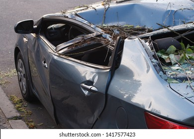 Minsk, Belarus -  June 06, 2019: Damaged car silver gray KAI RIO with the fallen tree parked on the city street