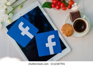 Minsk, Belarus. June, 2018. Ipad Apple is on the table. Paper printed Facebook logo is on it. Concept. Summer morning. Cup of coffee and candy. Breakfast with social network.