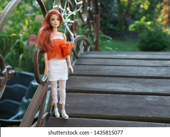 Minsk, Belarus. June, 2019. The most popular toy in the world Barbie doll. She stands in the garden on the bridge near the pond. Summer. Concept. Fashionista. Fashion-monger.