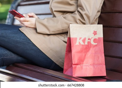 Minsk, Belarus, june 21, 2017: paper bag KFC on a bench next to a woman with a mobile phone. Kentucky Fried Chicken (KFC) is world's second largest restaurant chain almost 20,000 locations globally.