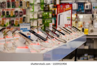 Minsk, Belarus - June 5, 2018: New smartphones on a white showcase with antitheft system in electronic store.
