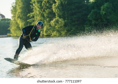 MINSK, BELARUS - June 8, 2017: Young slim man makes an extreme jump on wakeboarding. Concept of active lifestyle