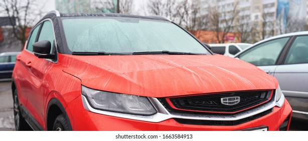 Minsk, Belarus - Mar 2020. Red Geely Coolray SX11 front view of new Compact SUV. Shiny, modern Geely car grill with water drops due to driving in rain. Head lamps of Geely Coolray, compact sport SUV