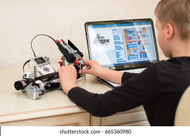 Minsk, Belarus - March 11, 2017: Boy teenager behind the desk programs Lego robot on the Sony laptop in Scratch program. E-learning. Stem education. Modern education for genius kid.