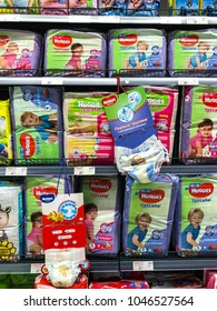 """Minsk, Belarus - March 13, 2018: Shelves with diapers under the brand """"Huggies"""" of baby diapers for sale in supermarket. The trademark belongs to the company Kimberly-Clark Corporation since 1978"""