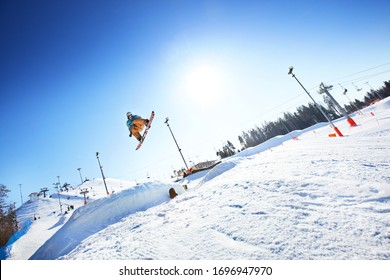 Minsk, Belarus- March, 2012: Snowboarder jumping through air with deep blue sky in background
