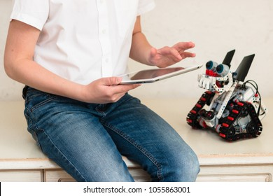Minsk, Belarus - March, 2018: The schoolboy sits on the table and controls the Dragon-dog robot on the tablet iPad Apple. Lego robot. Stem education. AI.