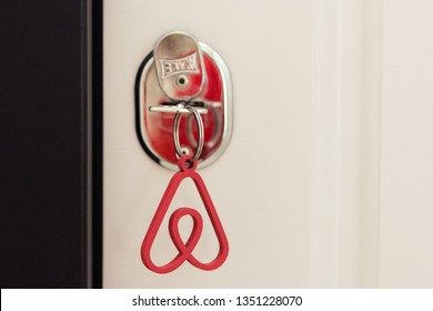 Minsk, Belarus. March, 2019. The key to the apartment or house with the key pendant in the form of the logo of the famous international rental company Airbnb for travelers. The idea of business.