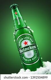 MINSK, BELARUS - MARCH 26, 2019: Cold bottle of Heineken Lager Beer with ice over green background. Heineken is the flagship product of Heineken International