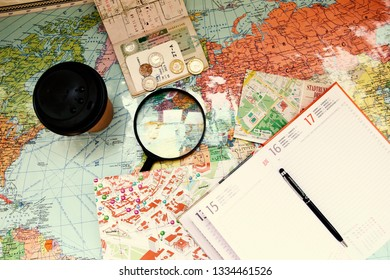 Minsk/ Belarus - March 6 2018: Flat lay photo with magnifying glass, notepad, documents and money on the map in russian. Travel concept