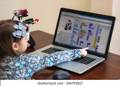 Minsk, Belarus - March 8, 2017: Little girl behind the desk programs Lego robot on the laptop ASUS in Scratch program.
