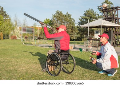 Minsk, Belarus, MAY 1, 2019 - a disabled person in a wheelchair shoots a skeet in a sports club with a shotgun along  (with an instructor)