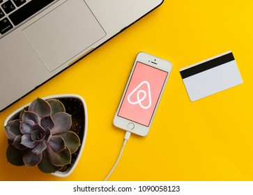 MINSK, BELARUS - May 11, 2018: Top view of white iphone with Airbnb logo on display. Flat lay with credit bank card, laptop, succulent plant and smartphone on the yellow table as background.